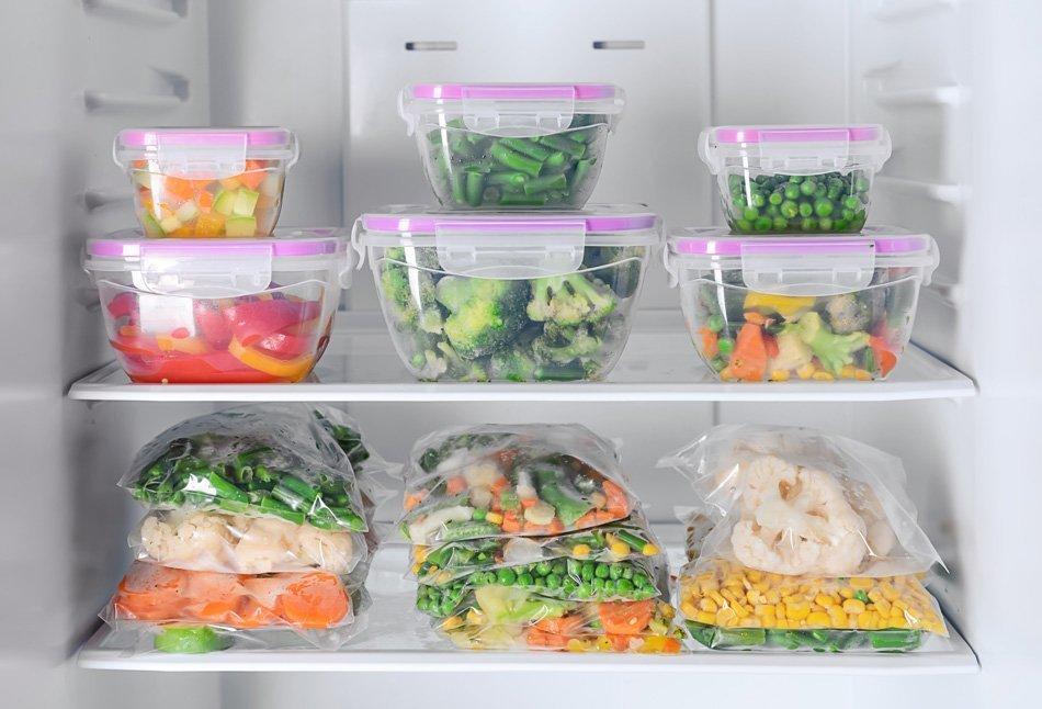Posode in plastične vrečke, napolnjene s sadjem in zelenjavo v hladilnikus sadjem in zelenjavo v hladilnikuz zamrznjeno zelenjavo v hladilniku
