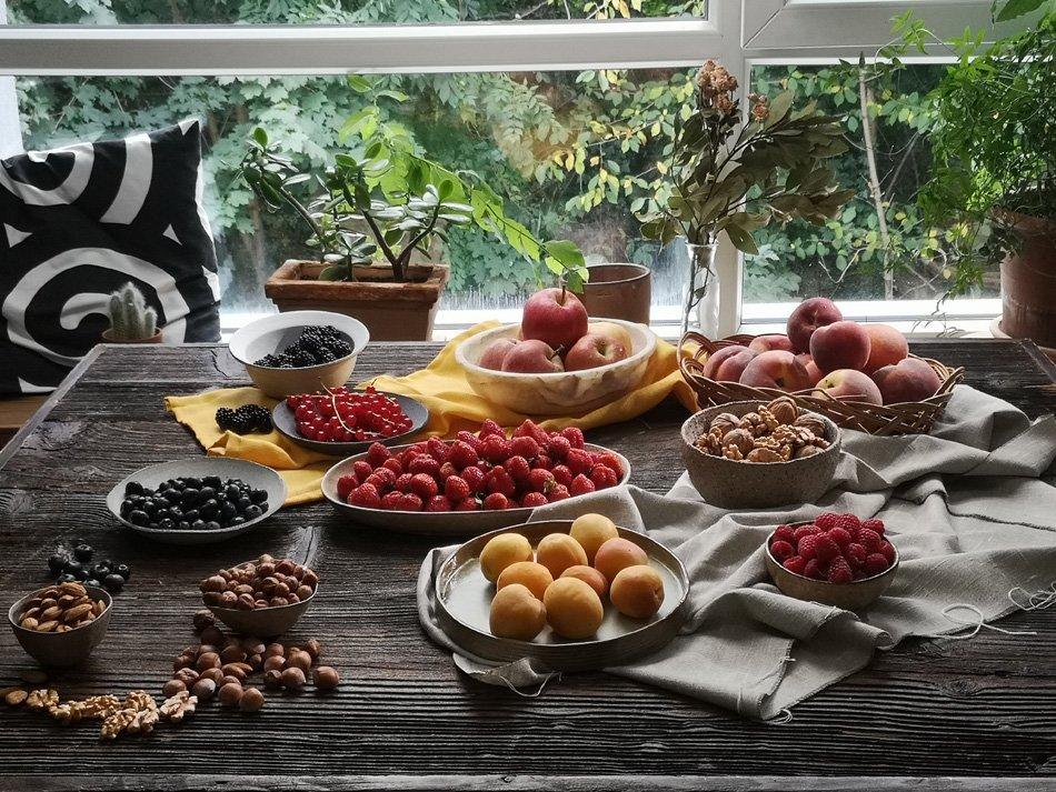 Gozdni sadeži, plodovi in sadje na mizi ob oknu