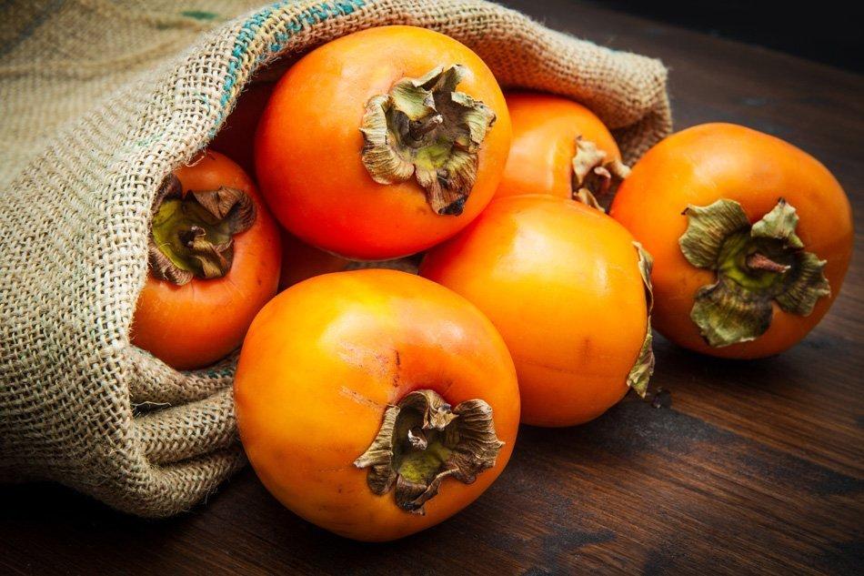 Okusno sveže sadje kakija na leseni mizi