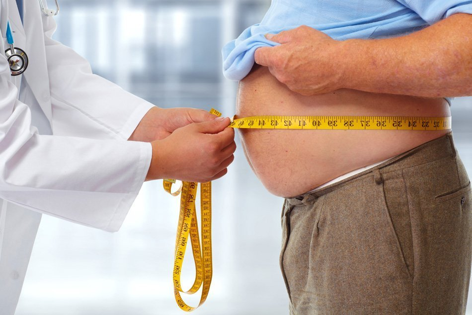 Zdravnik meri debel moški trebuh.