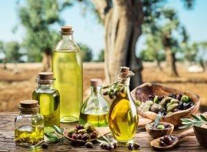 Oljčno olje na mizi - v ozadju oljčni nasad