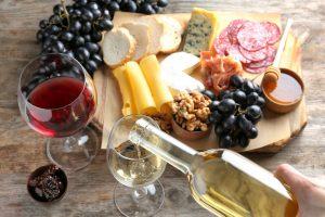 Ženska naliva belo vino v kozarec na mizi z okusno hrano