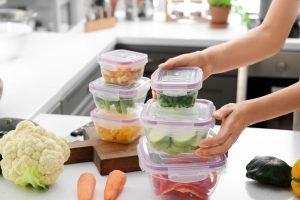 Ženska drži kup plastičnih posod s svežo zelenjavo za zamrzovanje za mizo v kuhinji