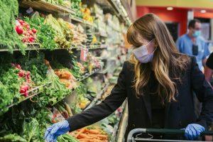 Ženska z masko, ki nosi lateks rokavice med nakupovanjem v supermarketu med karanteno koronavirusa