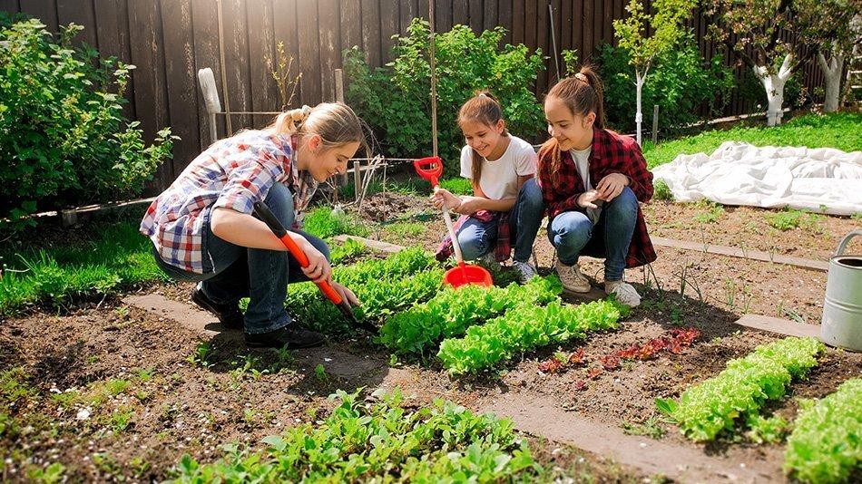 Mlada ženska s hčerama, ki sadijo semena na vrtu