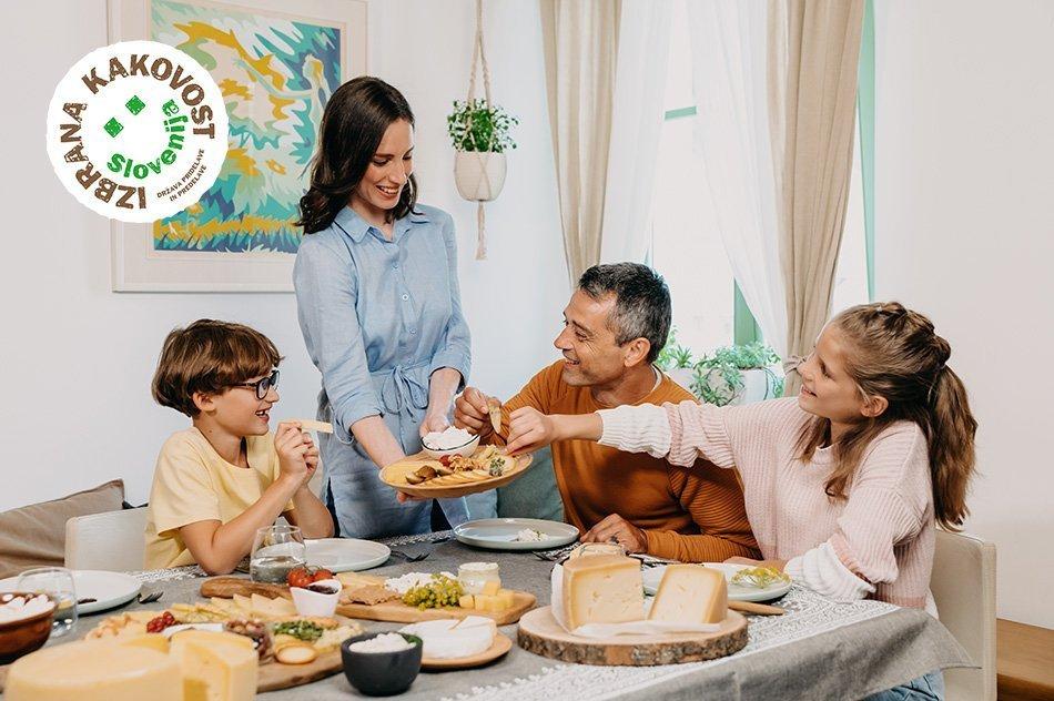 Družina ob obloženi mizi z mlečnimi izdelki